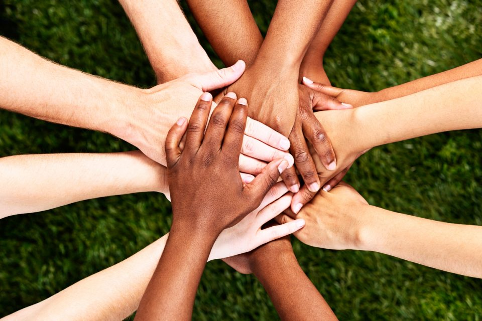Multicultural hands atop one another